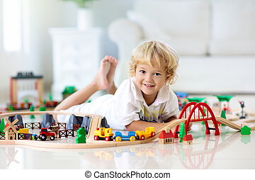 Kids play wooden railway. Child with toy train.
