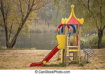 Kids playground set on sandy lake shore in city park