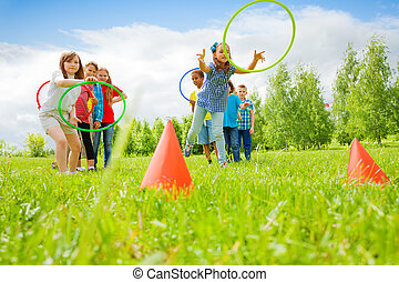 Kids playing and throwing colorful hoops on cones while ...