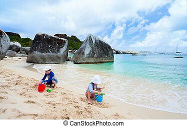 Kids wearing sun protection rash guard at beach during summer vacation