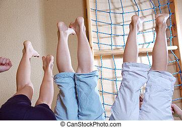 Kids having fun at home. Three pairs of legs.