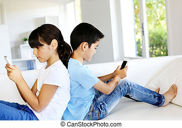 Kids playing at home with smartphones