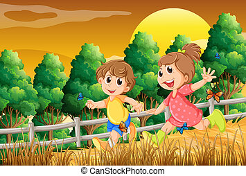Kids playing at the forest near the wooden fence