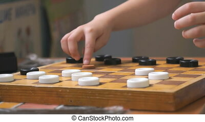 Kids sit at the table and play checkers at the garden. Close-up