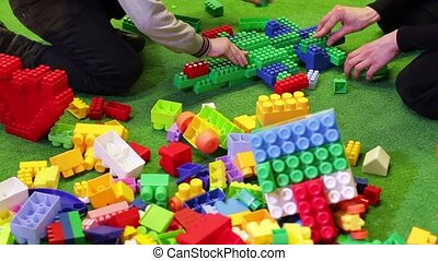 Kids playing constructor. Children playing with colorful...