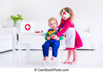 Kids playing doctor - Two happy children, cute toddler girl...
