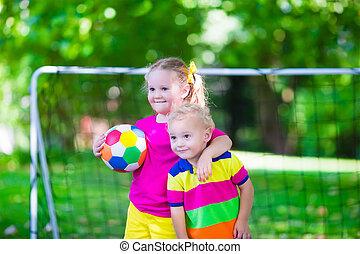 Kids playing football in school yard - Two happy children...