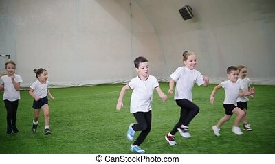 Kids playing football in the indoor football arena. Running....