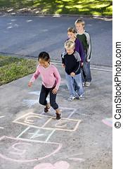 Kids playing hopscotch - Asian girl jumping on hopscotch...