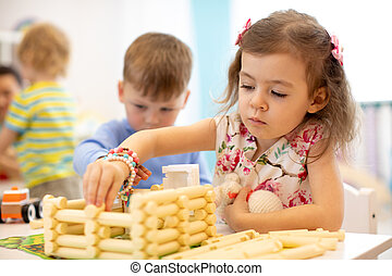 Kids playing in kindergarten. Children building toy house with plastic blocks sitting together by the table