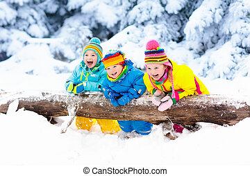 Kids playing in snow. Children play outdoors in winter ...