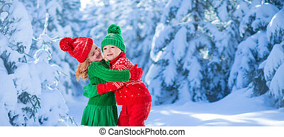 Kids playing in snowy winter forest - Little girl and boy in...