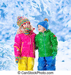 Kids playing in snowy winter park - Little girl and boy in...