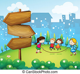 Kids playing in the hills with a wooden signboard