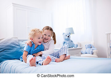 Kids playing in white bedroom - Happy kids playing in white...