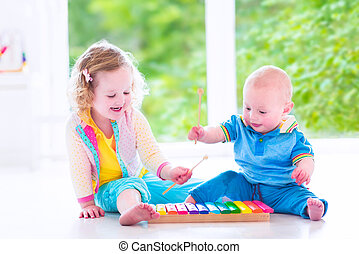 Kids playing music with xylophone - Two little children -...