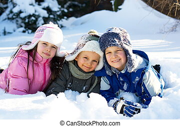 Kids Playing On a Winter Day - Three children lay on the...