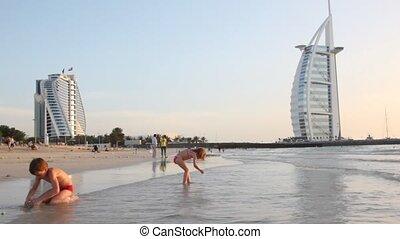 Kids playing on beach near Burj Al Arab five-star hotel during sunset