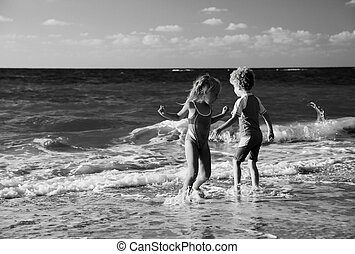 kids playing on the beach at sunset