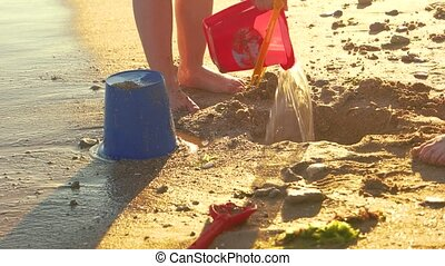 Kids playing on the seashore. Child stomping mud. How to...