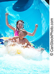 Kids playing on water slide - Happy young boy and girl...