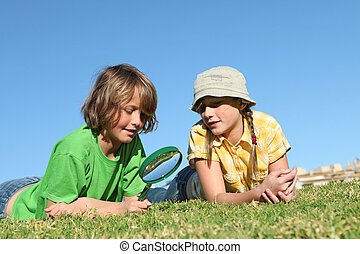 kids playing outdoors with magnifying, glass