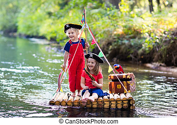 Kids playing pirate adventure on wooden raft - Kids dressed...