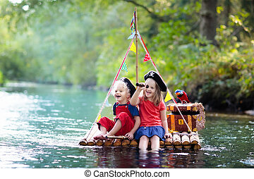 Kids playing pirate adventure on wooden raft - Kids dressed...