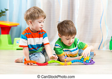 kids playing rail road toy in nursery
