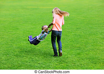 Kids playing together on the park grass