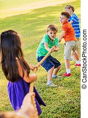 Kids Playing Tug of War On Grass - Group of Kids Playing Tug...