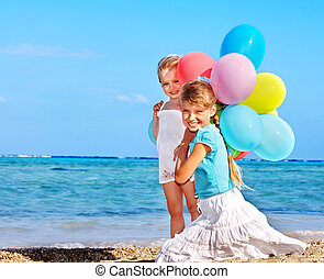 Kids playing with balloons at the beach