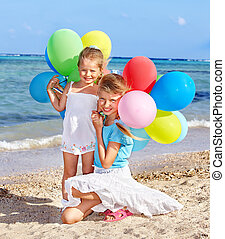 Kids playing with balloons at the beach.