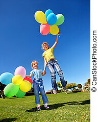 Kids playing with balloons in park.