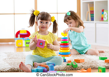 Kids playing with blocks together. Educational toys for preschool and kindergarten child. Little girls build toys at home or daycare.