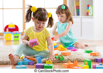 Kids playing with colorful block toys. Children building towers at home or daycare centre. Educational child toys for preschool and kindergarten.