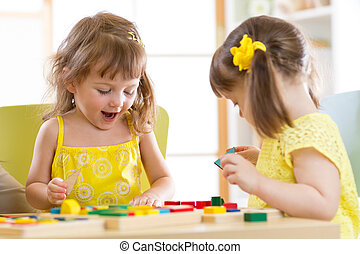 Kids playing with colorful block toys. Two children girls at home or daycare center. Educational child toys for preschool and kindergarten.