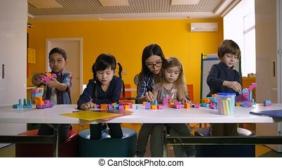 Kids playing with construction blocks in classroom