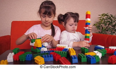 Kids playing with constructor. Emotions of little girls.