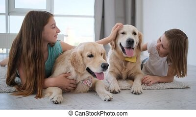 Kids playing with dogs in light room