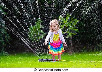 Kids playing with garden sprinkler