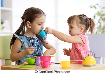 Kids playing with plastic tableware at home or daycare center