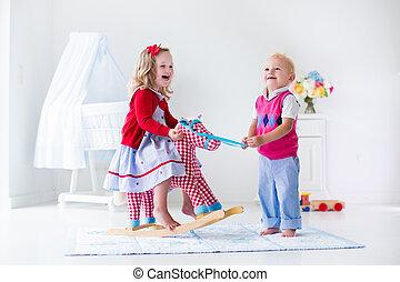 Kids playing with rocking horse - Two children play indoors....
