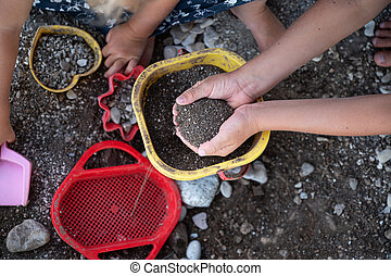 Kids playing with sand and dirt  and plastic toys