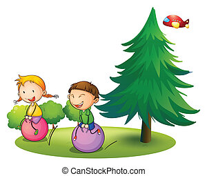 Kids playing with the bouncing balloons near the pine tree