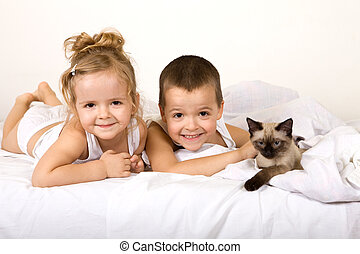Kids playing with their kitten on the bed