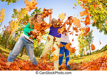 Kids playing with thrown leaves in the forest