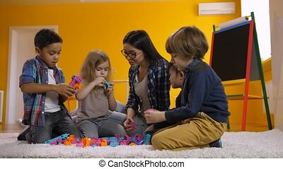 Kids playing with toy blocks in kindergarten
