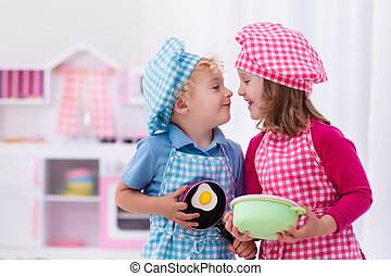 Kids playing with toy kitchen