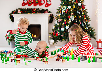 Kids playing with toy railroad on Christmas morning - Happy...